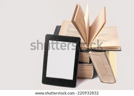 Ebook reader and old books isolated on white - stock photo