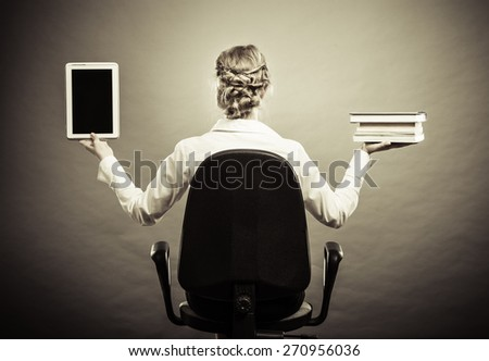Ebook vs book. Woman sitting on chair holding traditional book and e-book reader tablet touchpad pc back view grunge background. - stock photo
