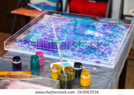 Ebru marbling on water surface in basin, accessories for art - stock photo