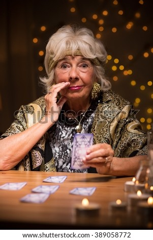 Eccentric mysterious elderly lady with tarot cards - stock photo