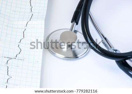 ECG paper tape stethoscope on white background close-up front view. Diagnosis and treatment of diseases of the heart electrical conduction system and rhythm disturbances such as arrhythmia, blockade