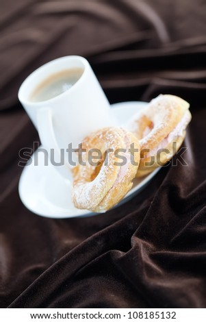 Eclairs  close-up on a plate with a cup of coffee