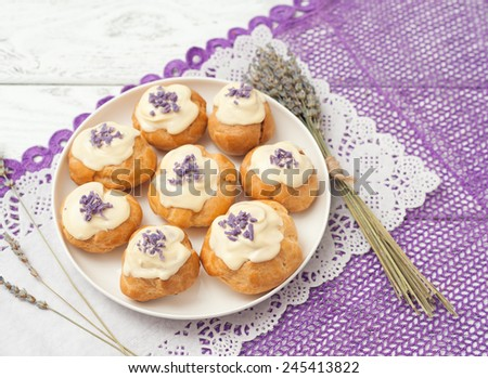 eclairs with lavender custard cream on wooden background - stock photo