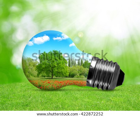 Eco bulb in grass. Environment or energy concept background. - stock photo