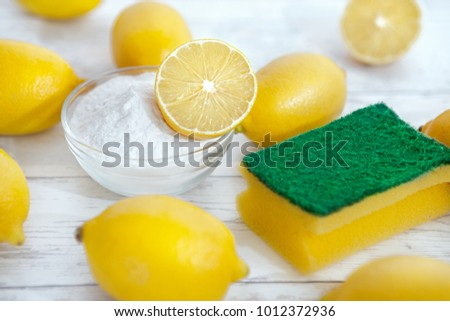 Eco cleaners baking soda, lemons and sponge on the table
