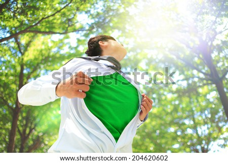 ECO concept - Business man opens his shirt to show off his green copy space in forest trees - stock photo
