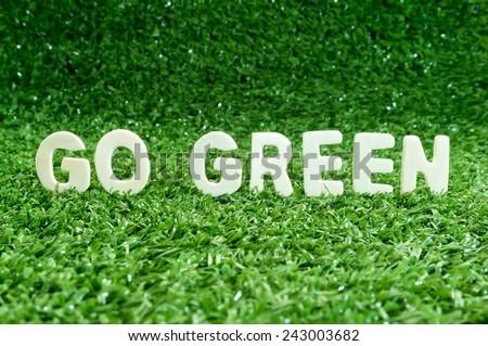Eco concept. Go green wooden words on artificial grass - stock photo