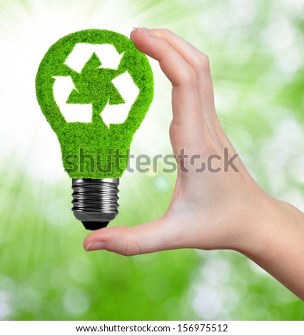 eco energy bulb in hand on green background  - stock photo