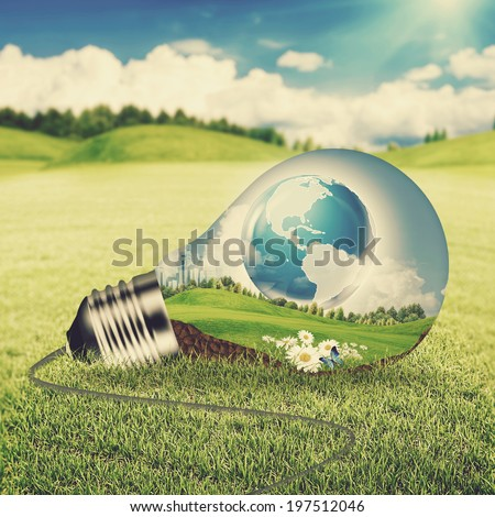 Eco energy concept. Light bulb with green world inside over natural backgrounds with shallow DOF - stock photo