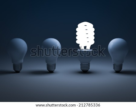Eco energy saving light bulb , one glowing compact fluorescent lightbulb standing amongst the unlit incandescent bulbs , the different concept - stock photo