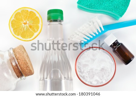 Eco-friendly natural cleaners. Vinegar, baking soda, salt, lemon and essential oil. Homemade green cleaning on white background. - stock photo
