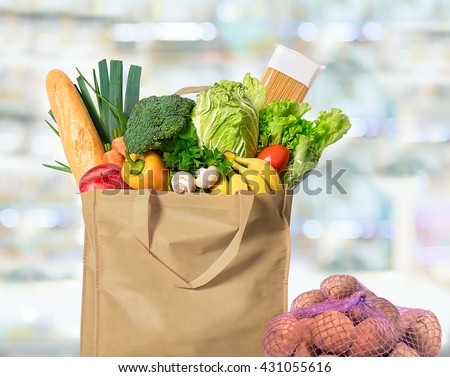 Eco friendly reusable shopping bag filled with vegetables and potatoes in a string bag