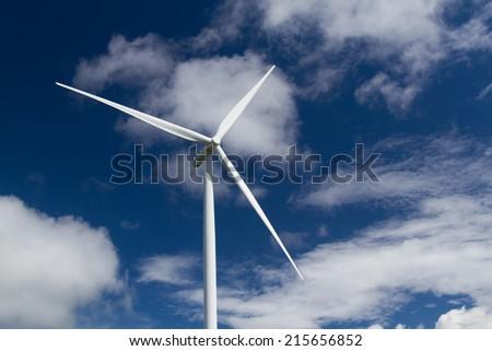 Eco Power, Wind turbine over the blue clouded sky  - stock photo