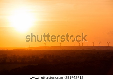 Eco power. Wind turbines with sun background - stock photo