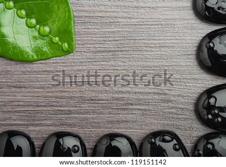 Eco spa background wooden with frame of stones and leaf with water droplets, space for your text - stock photo