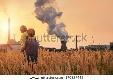 Ecological concept image. Father with son looking on chemical plant emissions at sunset time