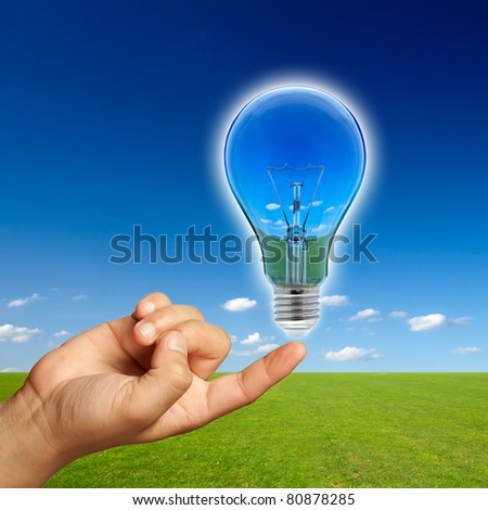 Ecological concept, reflection of nature in lamp with hand. - stock photo