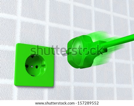 ecological european green plug is going into a green socket placed on the wall - stock photo