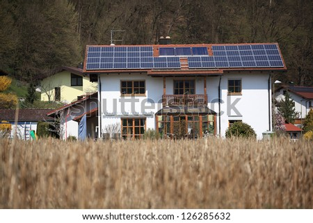 Ecological family house with many solar panels on the roof - stock photo