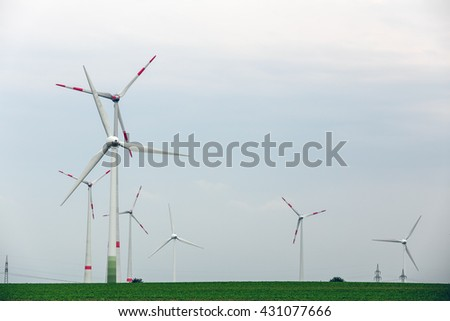Ecological power with windmill on the field.Yard of windmill power generatorunder blue sky, shown as energy industry concept.Wind turbines generating electricity. - stock photo