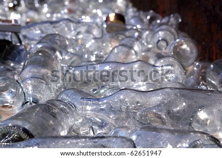 ecological recycling glass bottles in messy container - stock photo