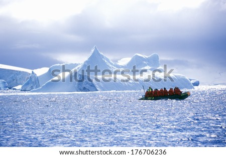 Ecological tourists in inflatable Zodiac boat in Errera Channel at Culverville Island, Antarctica