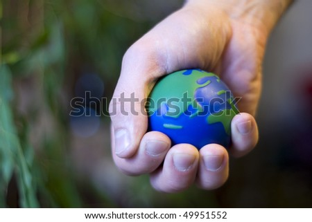 Ecological vision where human hand squeeze our planet - stock photo