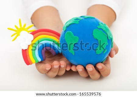 Ecology concept - a clean earth in child hands with colorful rainbow made of clay - stock photo