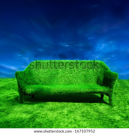 Ecology concept background. Grassy sofa standing at green grass over blue sky - stock photo