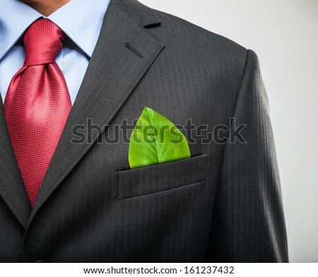 Ecology concept, businessman keeping a green leaf in his pocket - stock photo