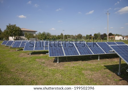 Ecology electric energy farm with solar panel battery in green field - stock photo
