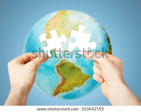 ecology, energy saving, people and environment concept - close up of male hands trying to connect white puzzle pieces over earth globe on blue background - stock photo