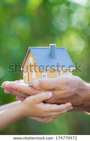 Ecology house in hands against spring blurred background - stock photo