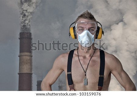 ecology, the man in the respirator against the backdrop of fuming pipe - stock photo