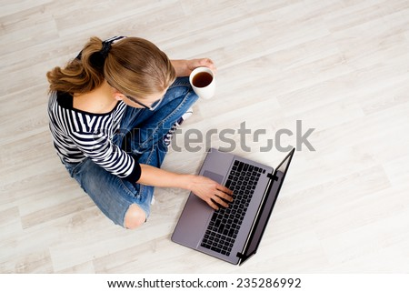 Ecommerce woman. Young female using computer for online shopping, sitting on the floor and drinking coffee. - stock photo