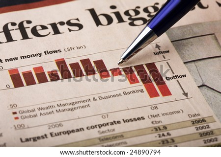 Economic and investment banking statistics printed in a financial newspaper. Analysis of the information with a pen pointed at bar chart showing money flow. - stock photo