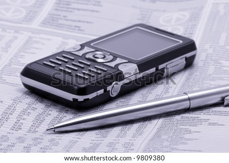 economic newspaper with pen and mobile phone - stock photo