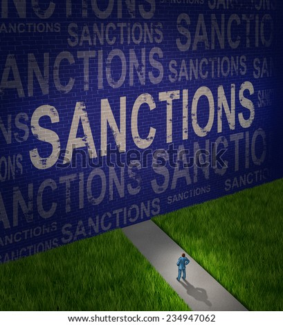 Economic sanctions as a global economy symbol for problems with political trade disputes as a man in front of a brick wall with words as a metaphor for government challenges resulting in isolation. - stock photo