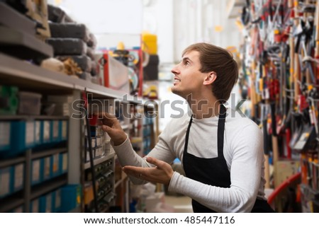 economic young salesman in apron with tools in supermarket
