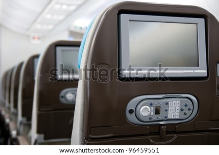 Economy class seats with entertainment system onboard a wide-body airliner. Shallow depth of field with the first seat in focus. - stock photo