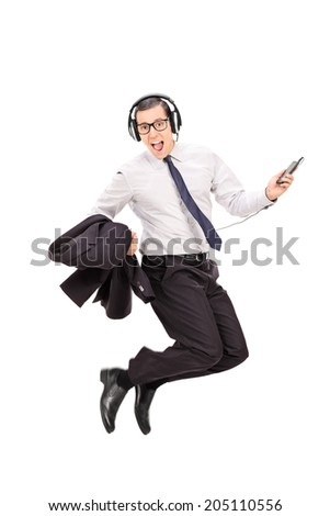 Ecstatic businessman listening to music on his cell phone isolated on white background - stock photo