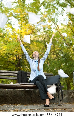 ecstatic businesswoman sitting on bench in park and  throwing paper in the air - stock photo