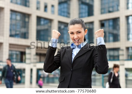 ecstatic businesswoman with arms raised in front of office buildings - stock photo