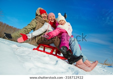 Ecstatic family on sledge having fun in winter - stock photo