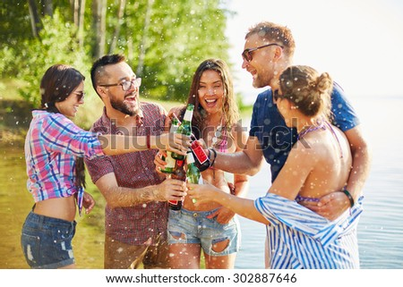 Ecstatic friends toasting with beer in water splashes - stock photo