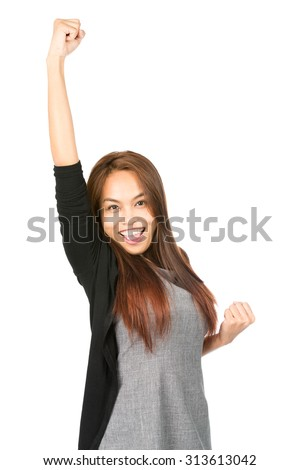 Ecstatic, good looking Asian woman in casual clothes, yelling, celebrating with winning arm raised, fist thrust in air looking at camera with euphoric smile. Thai national of Chinese origin. Half
