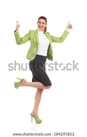 Ecstatic mid adult woman with thumbs up. Shouting business woman dancing on one leg and showing thumbs up. Full length studio shot isolated on white. - stock photo