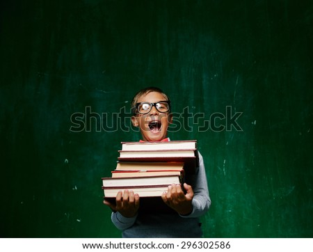 Ecstatic schoolboy in eyeglasses holding books - stock photo