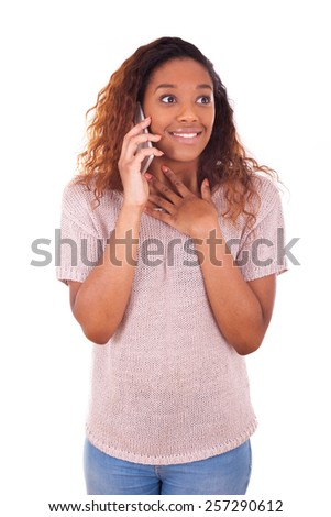 Ecstatic young African American woman making a phone call on her smartphone