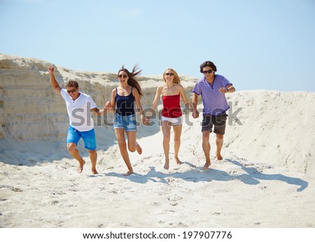 Ecstatic young people running on the sand of beach - stock photo
